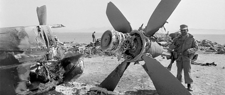 An Iranian soldier examines the wreckage of a US C-130 Hercules plane in a desert near Tabas. (File photo)